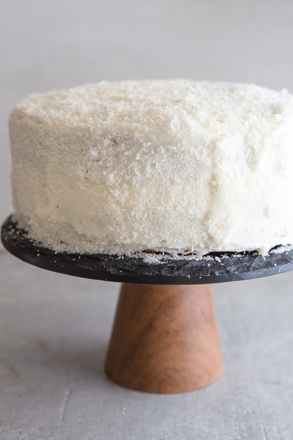 coconut layer cake on a black cake stand