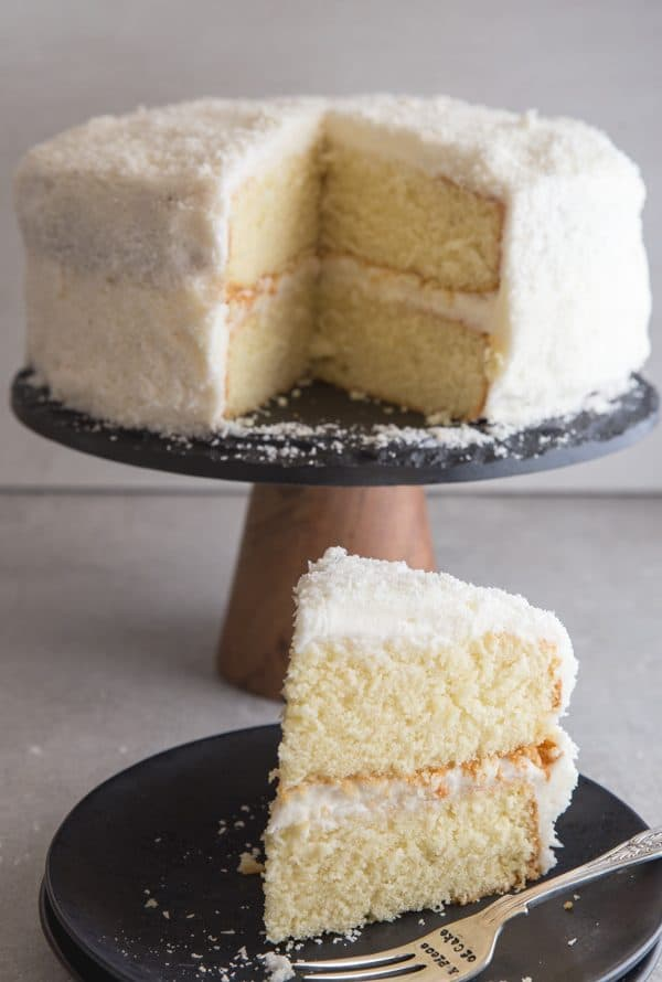 coconut cake with a slice on a black plate