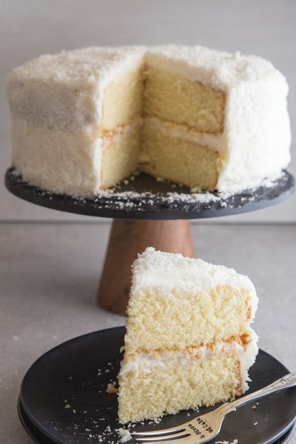 coconut layer cake with a slice on a black plate