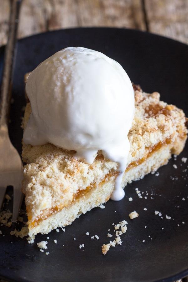 a slice of crumb pie with a scoop of vanilla ice cream