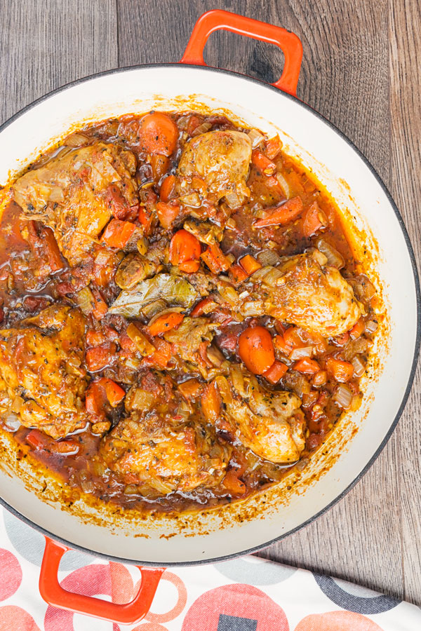 chicken cacciatore in a white and red pan