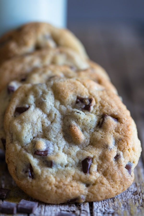 chocolate chunk cookies leaning against a bottle of milk