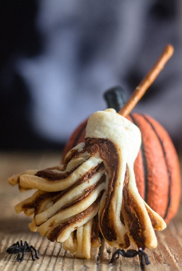 witches brooms puff pastry leaning against a pumpkin