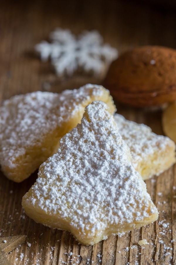 Italian almond cookies sprinkled with powdered sugar on a wooden board