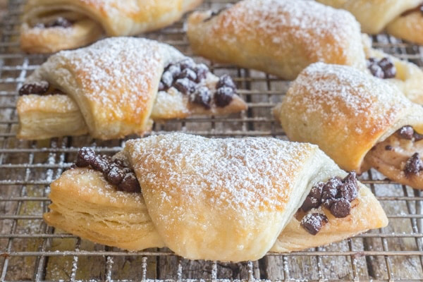 Baked crescents dusted with powdered sugar on a wire rack.