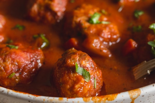 up close Italian meatballs with a pepper sauce in a white pan