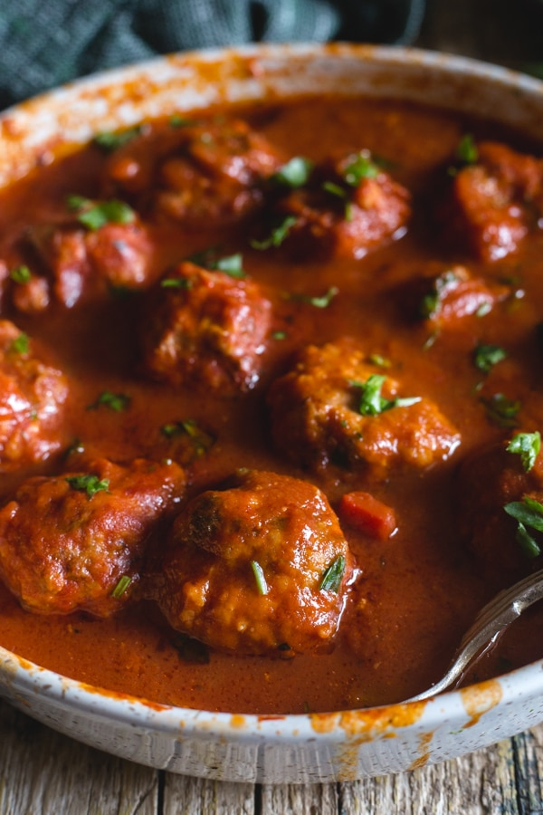 Italian meatballs in a red sauce in a white pan