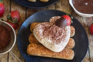 up close classic tiramisu heart shaped with a chocolate dipped strawberry