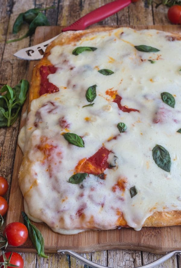 no knead pizza dough baked margherita pizza on a wooden board