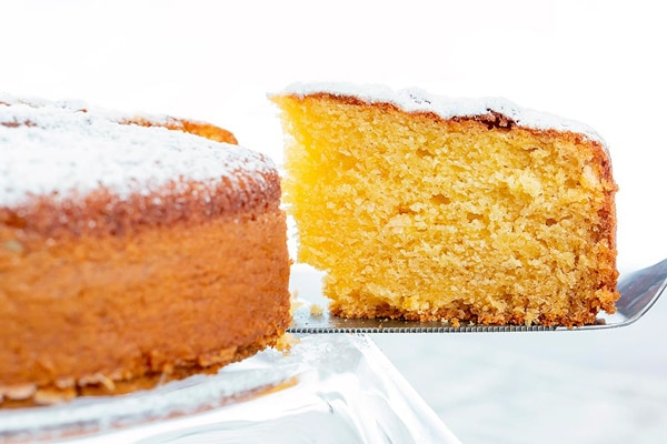 orange cake with a slice on a silver spatula