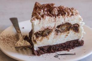 upclose tiramisu cheesecake slice on a white plate