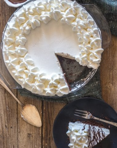 baileys mousse pie on a wooden board with a slice on a black plate