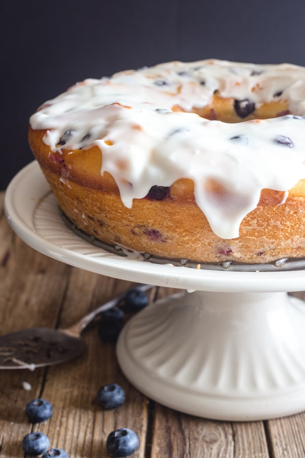 blueberry cake on a white stand with vanilla glaze