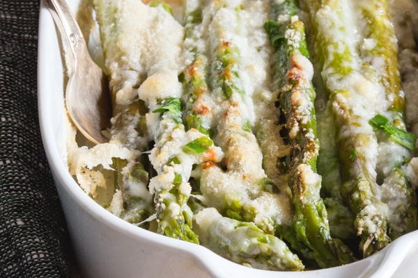 up close baked asparagus in a white baking dish
