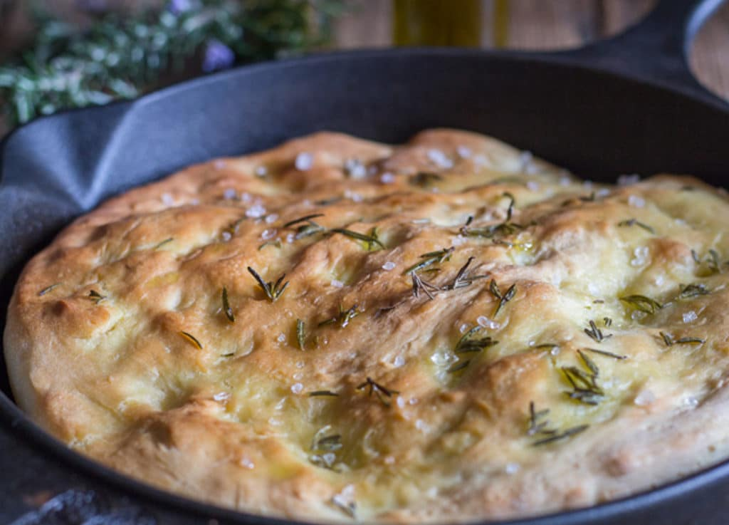 Baked focaccia in a black pan.