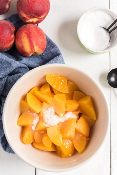 mixing peach slices and sugar in a white bowl