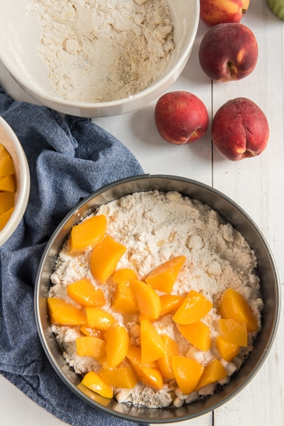 adding the peach slices on top of the crumb mixture in a black cake pan