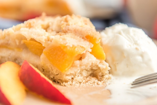 a slice of peach cake with a bit taken out on a plate with a scoop of vanilla ice cream and 2 slices of peaches