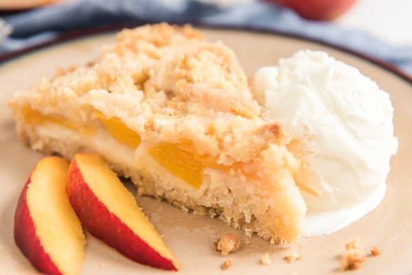 a slice of peach cake on a plate with a scoop of vanilla ice cream and 2 slices of peaches