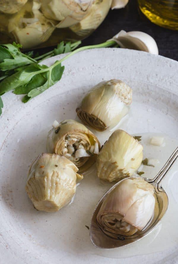 artichokes under oil on a white plate