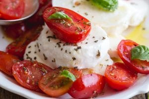 up close tomato caprese on a white plate