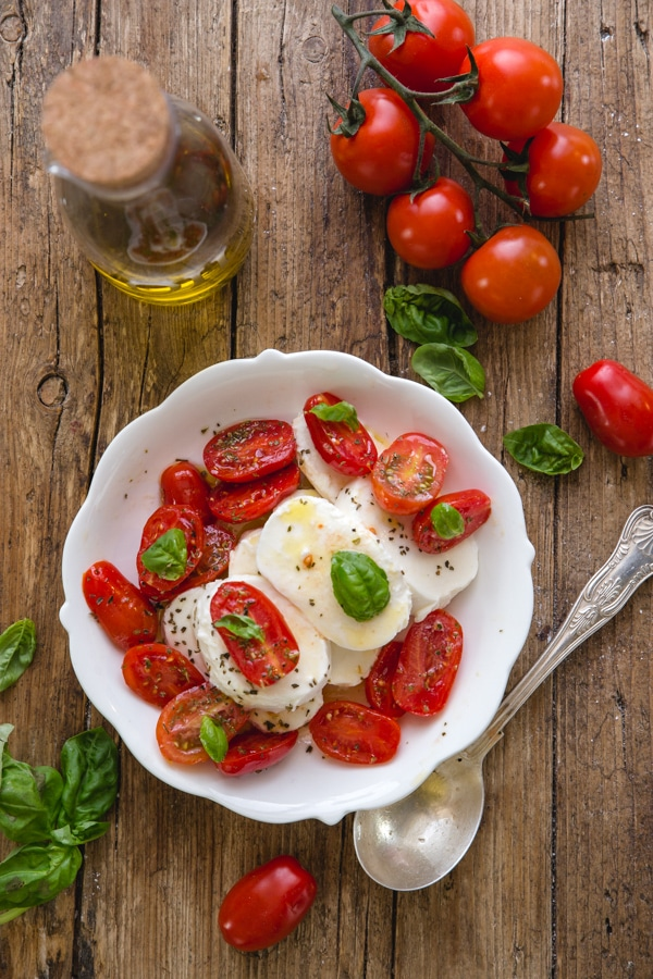 caprese salad in a white bowl on a wooden board with oil and tomatoes