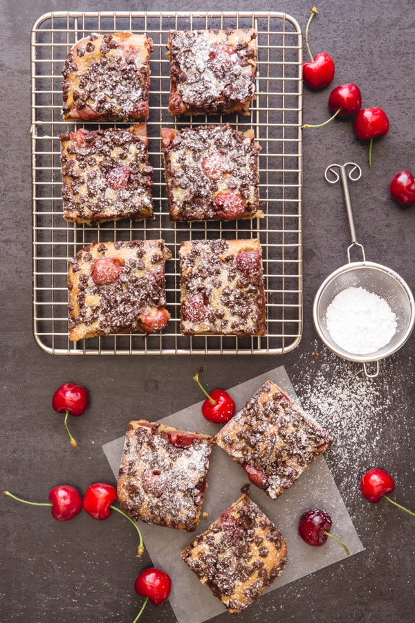 cherry blondies on a wire rack and on parchment paper