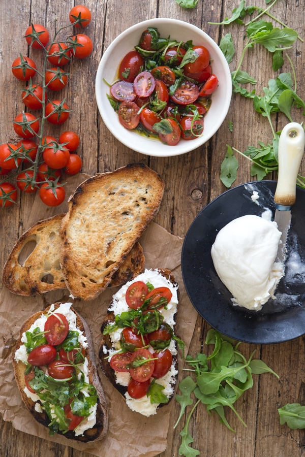 burrata bruschetta on a board with grilled bread fresh tomatoes and burrata on a black dish