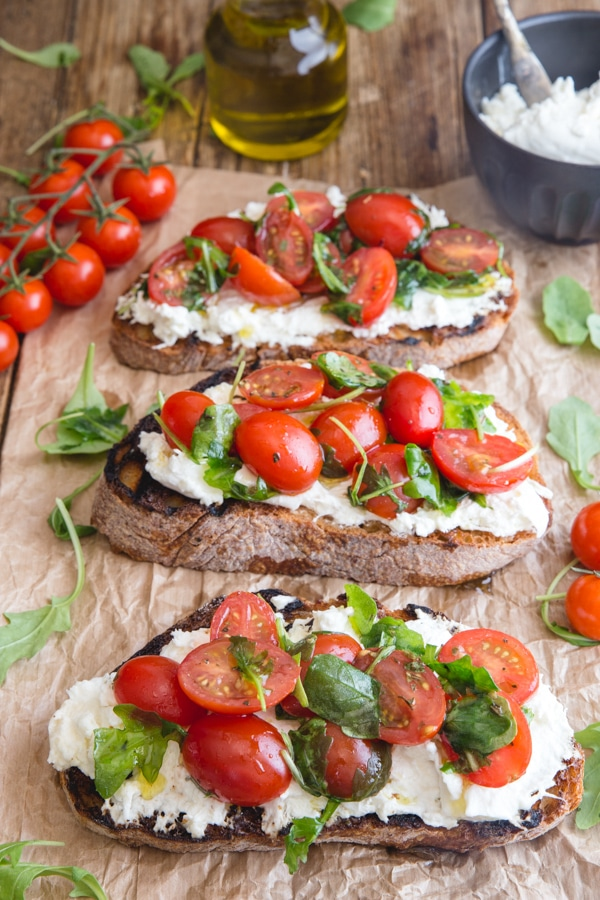burrata bruschetta on a brown paper with fresh tomatoes