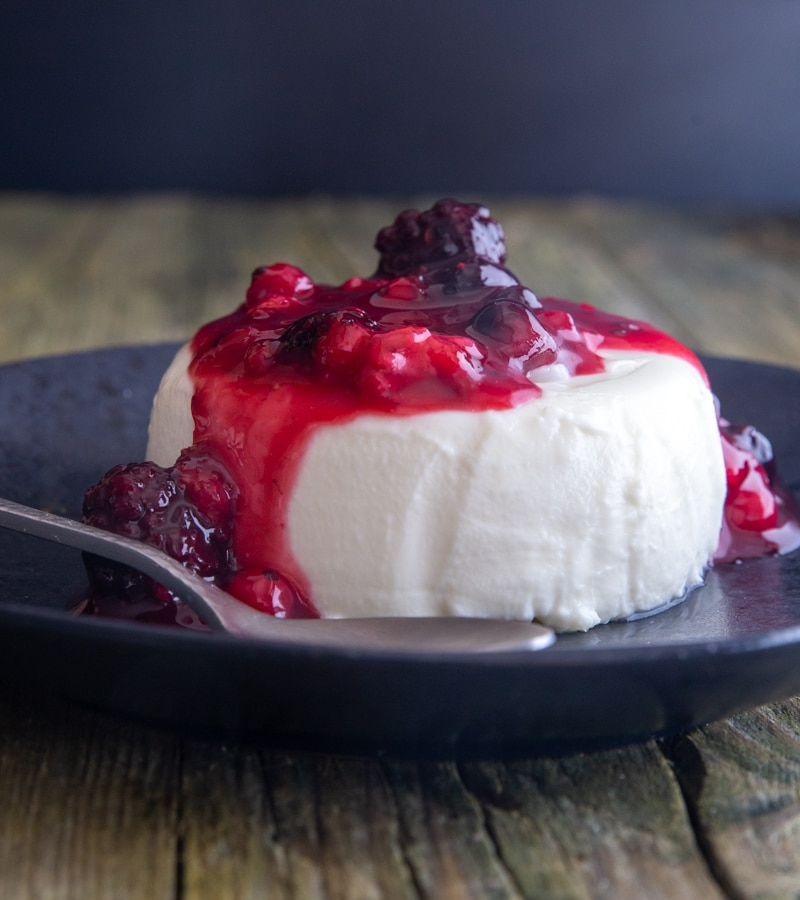 Panna cotta with a fruit topping on a black plate with a silver spoon.