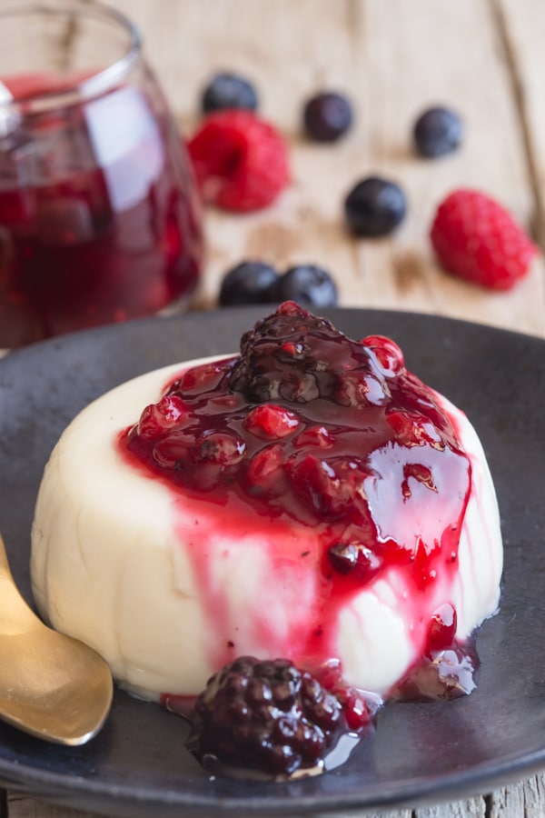 panna cotta with a berry sauce on a black plate