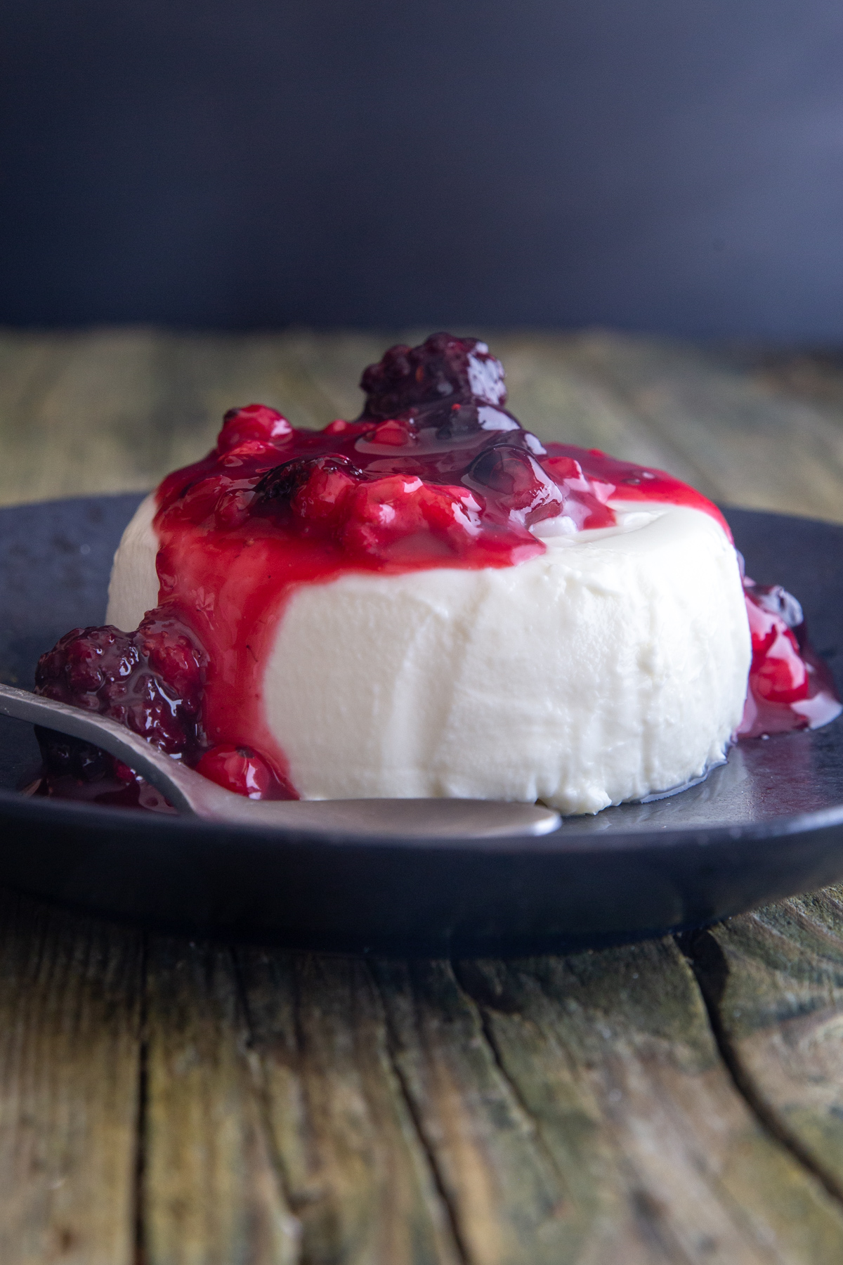 Panna cotta on a black plate with berry sauce.