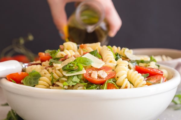 adding olive oil to a bowl of pasta salad