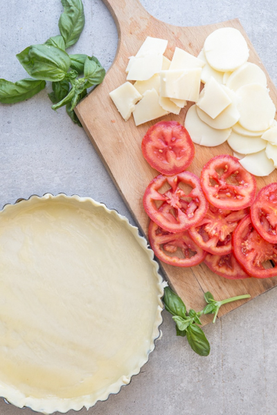 The crust in the pie plate & the cheese & tomatoes sliced on a board.