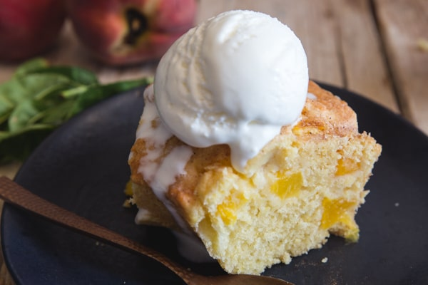 up close slice of peach cake with a scoop of ice cream on a black plate