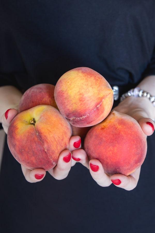Vanessa holding 4 peaches