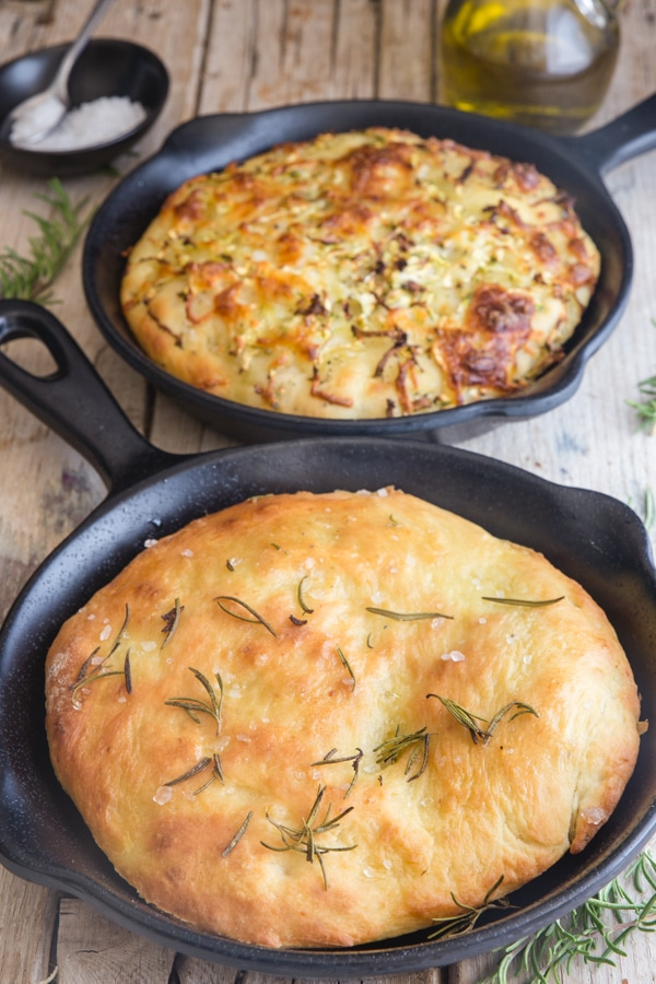 potato focaccia in 2 black pans, rosemary & zucchini and cheese
