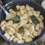ricotta gnocchi with sage leaves in a black pan