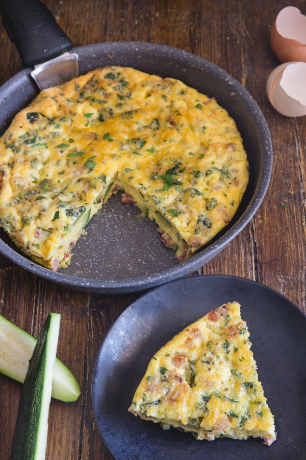 baked frittata in a black pan and a slice on a black plate