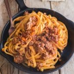 bolognese sauce with pasta in a black pan