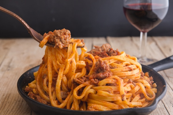 a fork of pasta and bolognese sauce