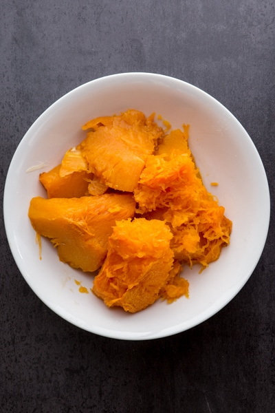 pulp removed from the skin of the pumpkin chunks and placed in a white bowl