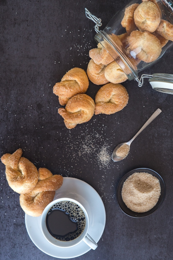 Italian twist cookies on a black board with a coffee in a white cup and brown sugar in a bowl and on a spoon
