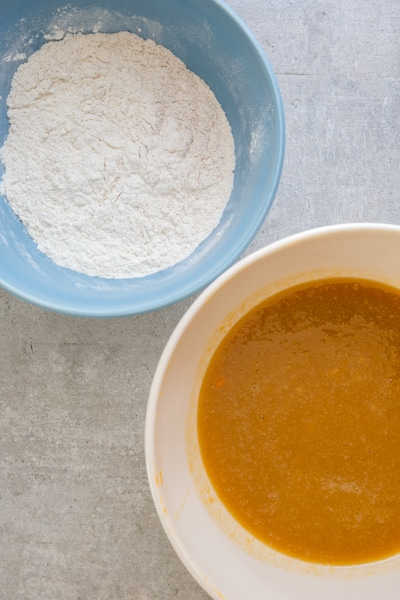dry ingredients whisked in a blue bowl and wet ingredients mixed in a white bowl for pumpkin bread