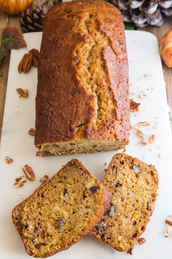 pumpkin bread with 3 slices on a marble cutting board and knife