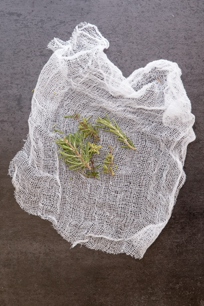 placing rosemary leaves and thyme in a cheesecloth square