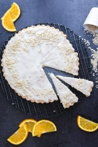 orange shortbread on a black wire rack with 2 pieces cut and orange slices around it