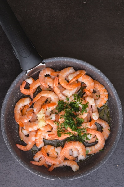 raw shrimp and fresh parsley in a black frying pan