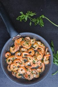 sauteed shrimp with parsley in a black frying pan