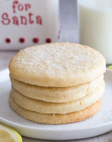 4 lemon sugar cookies on a white plate with a glass of milk and milk jar in the back